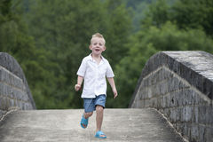 Summer time : little boy running on a bridge Royalty Free Stock Photography