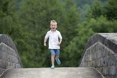Summer time : little boy running on a bridge Royalty Free Stock Photos