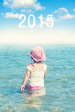 Summer time. Little child walking in the sea water with 2015 cloud sign Stock Images