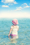 Summer time. Little child walking in the sea water and looking at horizon Royalty Free Stock Photography