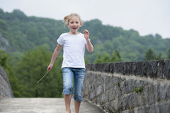 Summer time : little girl running on a bridge Royalty Free Stock Photography