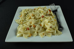 Summer time meal. Pasta on a white plate with a black back ground Stock Image