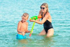 Mother and son play on the beach with water pistols. Summer time stock image