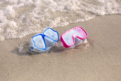 Summer time: Red and blue gogles on the sand by the ocean Stock Photos