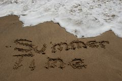 Summer Time Sand. It's always fun when it's summer time. Written in wet sand before a wave washed it away Stock Images
