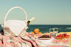Summer time at the sea. Romantic picnic on the beach - wine, str. Awberries and sweets. Selective focus Royalty Free Stock Photography