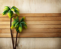 Summer time. Summer still life of two plastic palm trees on a wooden background Stock Photos