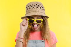 Summer time, a teen girl in a straw hat and sunglasses winks one eye, shows the language on a yellow background stock image