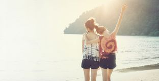 Summer time, Two girls hugging their necks and turning their backs on the beach. In the evening, the sun from behind beautiful Royalty Free Stock Image