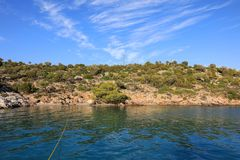 Summer time view on the Love bay Poros island coast from the yacht feed, Greece. Horizontal Stock Images