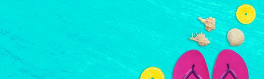 Summer time wide banner, purple flip flops, seashells and lemon pieces on vivid blue grunge background with space for text. Summer time wide banner, purple flip Royalty Free Stock Photography