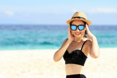 Summer time, woman in bikinis. Young beautiful woman on the beach. Young beautiful woman on the beach, Beautiful girl in sunglasses with hands near face on royalty free stock images