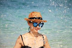 Summer time, woman in bikinis. Young beautiful woman on the beach. Young playful girl splashing on the beach, Woman with sunglasses in bikini royalty free stock images