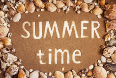 Summer time is written on the sand in frame of sea shells. Trave Stock Image