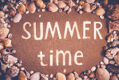 Summer time is written on the sand in frame of sea shells. Trave Stock Photo