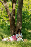 Summer time. Young woman at a picnic reading an e-book. Royalty Free Stock Photography