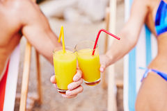 Summer toast. Woman and man holding drinks and toasting at resort Royalty Free Stock Photography