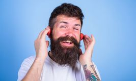 Summer top radio chart. Summer hit concept. Guy enjoy juicy sound summer hit song music. Man bearded hipster red ripe. Strawberry ears as headphones. Hipster Stock Images