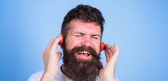 Summer top radio chart. Summer hit concept. Guy enjoy juicy sound summer hit song music. Hipster beard listen music. Strawberry earphones. Man bearded hipster Royalty Free Stock Images