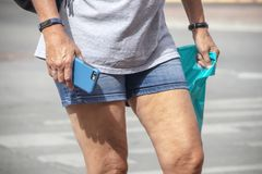 Summer tourist - Closeup of woman in blue jean shorts walking with fitness bracelet and phone in her hand and plastic bag from. Shopping in her other bag royalty free stock photography