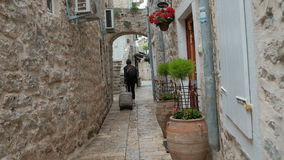 Summer tourists with a suitcase leaves the place to stay in old town. Among the stone buildings, a woman with a backpack and luggage leaves for the airport stock footage
