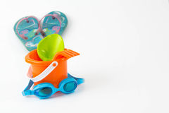 Summer toys bucket with spade goggles flip flops isolated Royalty Free Stock Photo
