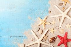 Summer travel background from seashell, starfish and sand on blue table top view. royalty free stock photography