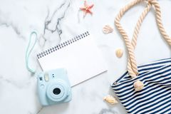 Summer travel composition on a marble background. Women`s desk with instant photo camera, striped beach bag, seashells and blank n royalty free stock photos
