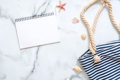 Summer travel composition on a marble background. Women`s desk with striped beach bag, seashells and blank notepad. Lifestyle of stock images