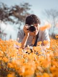Summer travel concept from front side of asian man traveler and. Photographer with black hair during take photo to flower field with sunny and soft focus Stock Photos