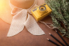 Summer travel concept with yellow toy camera with woman hat bran Stock Photography