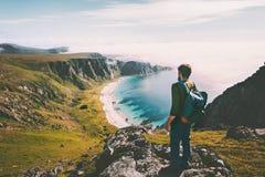 Summer travel man tourist standing alone on mountain top stock photo