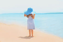 Summer travel photo pretty girl. In dress and hat enjoying on the beach near sea Stock Images