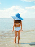 Summer travel photo pretty little girl in straw hat on the beach Royalty Free Stock Photo
