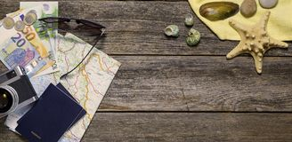 Summer travel stuff with seashells. Summer travel accessories on a wooden background with marine details. Passports, maps, camera and money Stock Photo