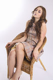 Summer travel. stylish model sitting on straw chair Royalty Free Stock Photography