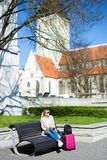 Summer travel and vacation concept - young woman sitting with suitcase in old town of Tallinn, Estonia royalty free stock images