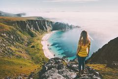 Summer travel woman tourist standing alone on mountain top over sea beach royalty free stock image