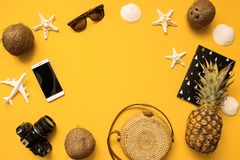 Summer traveler accessories flat lay. Straw hat, camera, bag, sunglasses, coconut, pineapple, plane, notebook and phone on yellow. Summer traveler accessories royalty free stock photo