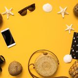 Summer traveler accessories flat lay. Straw hat, camera, bag, sunglasses, coconut, pineapple, plane, notebook and phone on yellow. Summer traveler accessories royalty free stock photography