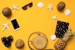 Summer traveler accessories flat lay. Straw hat, camera, bag, sunglasses, coconut, pineapple, plane, notebook and phone on yellow. Summer traveler accessories stock photography
