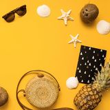 Summer traveler accessories flat lay. Straw hat, camera, bag, sunglasses, coconut, pineapple, plane, notebook and phone on yellow. Summer traveler accessories stock image