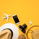 Summer traveler flat lay. Straw hat, retro film camera, bamboo bag, sunglasses, coconut, pineapple, phone on yellow background. Summer traveler accessories flat royalty free stock photo