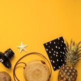 Summer traveler accessories flatlay. Straw hat, retro film camera, bamboo bag, sunglasses, coconut, pineapple on yellow background. Summer traveler accessories stock photography