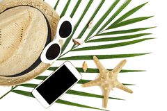 Summer traveler accessories: straw hat, sunglasses, starfish, tropical palm leaf on white background. Travel concept. royalty free stock photos