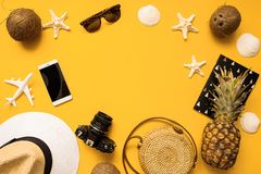 Summer traveler flat lay. Straw hat, retro film camera, bag, sunglasses, coconut, pineapple, plane,  and phone o yellow background. Summer traveler accessories stock photography