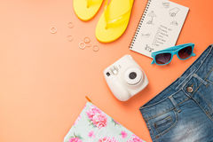 Summer traveling concept. Vacation accessories on orange background. stock photography