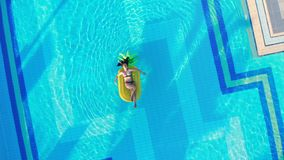 Summer traveling concept. Young woman relaxes on a yellow mattress, floating in a pool.