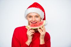 Summer treats on christmas party. Exotic christmas concept. Christmas girl eat watermelon. Exotic winter holiday. Girl. Wear santa hat eat slice watermelon stock image