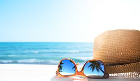 Summer tropical beach background; glasses and palm tree reflex stock image